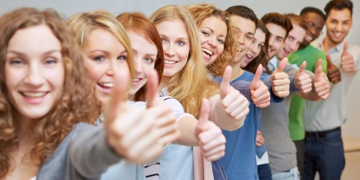 Viele lachende Schüler in einer Reihe halten ihre Daumen hoch