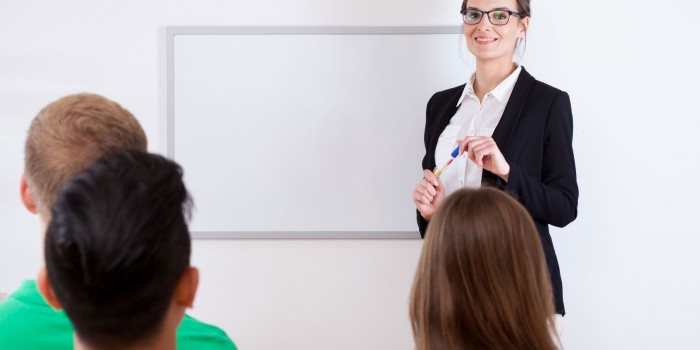 Students and female teacher in classroom, horizontal